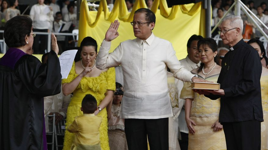 President Benigno Aquino III, center, takes his oath before Supreme Court Associated Justice Conchita Carpio-Morales as the Philippines' 15th President during inaugural ceremony Wednesday June 30, 2010, in Manila, Philippines. Mr. Aquino, the only son of Philippine democracy icons, the late President Corazon Aquino and assassinated opposition leader Sen. Benigno Aquino Jr., won by a landslide in the May 10 automated presidential elections. At right holding the Holy Bible is Jesuit priest Father Catalino Arevalo. (AP Photo/Bullit Marquez)
