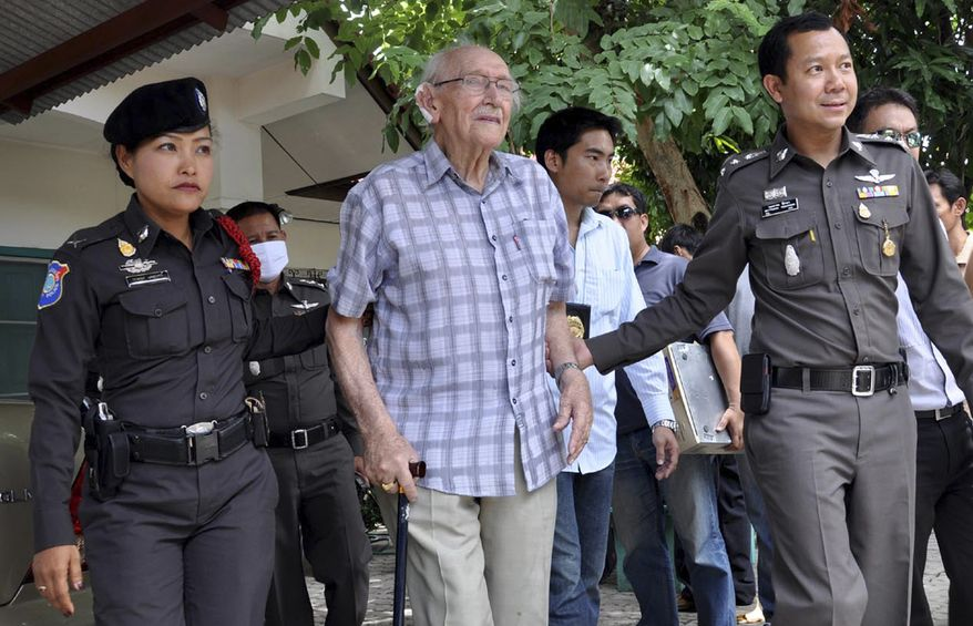 Australian Karl Kraus, center, is escorted by Thai policemen after being arrested, in Chiang Mai, Thailand, on Tuesday, June 29, 2010. Mr. Kraus was charged with raping and sexually abusing four underaged sisters, when one of them was as young as 5. (AP Photo/Wichai Thaprieo)