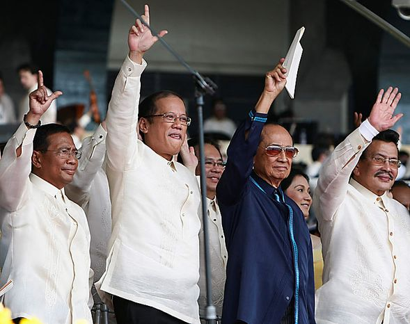 """President Benigno Aquino III, second from left, and Vice President Jejomar Binay, left, flash the """"L"""" signs for Laban (meaning Fight!) as former Presidents Fidel Ramos, second from right, and Joseph Estrada wave during a song number at the inaugural of Aquino Wednesday, June 30, 2010 in Manila, Philippines. Aquino was sworn in Wednesday as the Philippines' 15th president, leading a Southeast Asian nation his late parents helped liberate from dictatorship and which he promises to deliver from poverty and pervasive corruption. (AP Photo/Bullit Marquez)"""