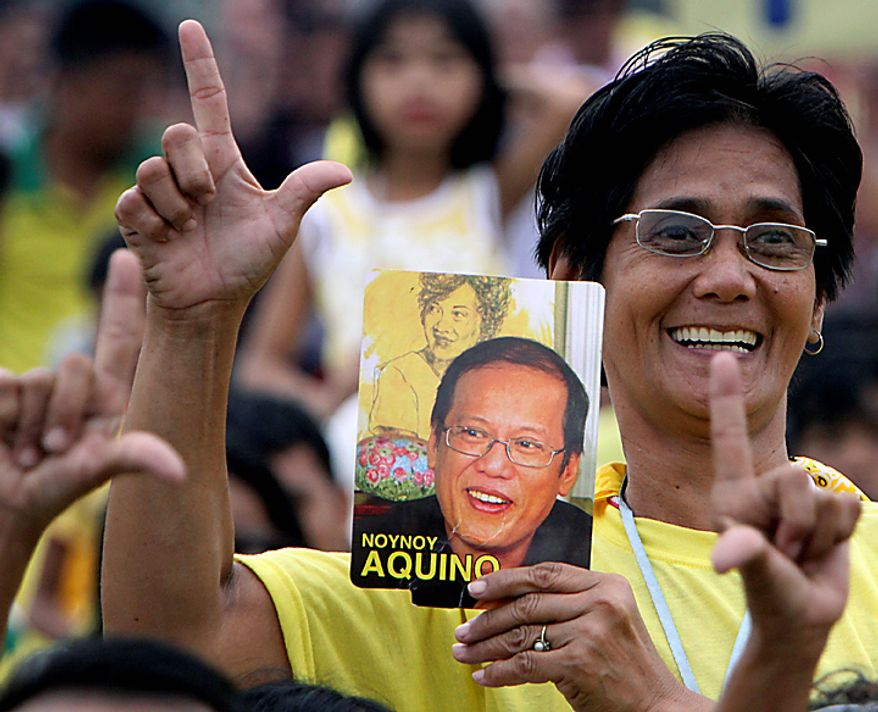 A supporters flashes the sign for Laban or Fight while displaying a picture of Benigno Aquino III during his inauguration ceremony Wednesday, June 30, 2010, at the Quirino grandstand in Manila, Philippines. Aquino was sworn in Wednesday as the Philippines' 15th president, leading a Southeast Asian nation his late parents helped liberate from dictatorship and which he promises to deliver from poverty and pervasive corruption. (AP Photo/Pat Roque)