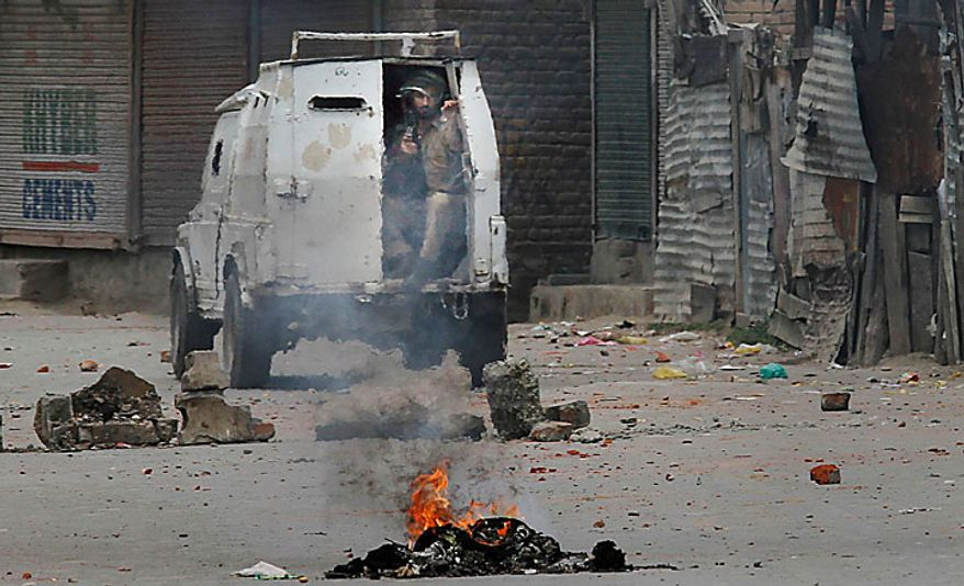 An Indian police vehicle patrols a road dotted with rocks and a burning tire set up as road blockade by protesters in Srinagar, India, Wednesday, June 30, 2010. Authorities brought new areas under curfew in the Indian portion of Kashmir on Wednesday to control the worst street violence in a year, triggered by the killing of 11 people allegedly by government forces over the past two weeks. (AP Photo/Dar Yasin)