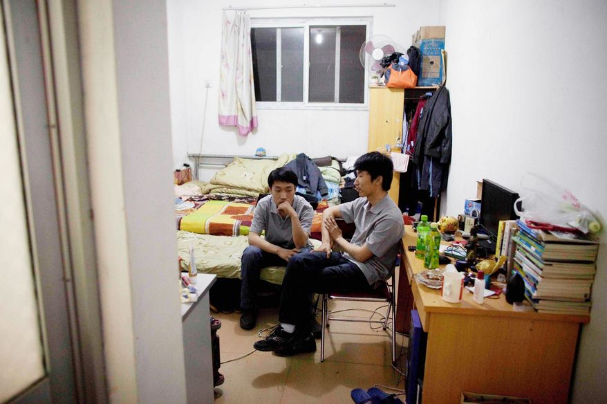 Liu Jun, 24, (right) and Li Zhenyang relax in their rented room in Beijing. Mr. Liu sleeps in a room so small that he shares a bed with two other men, a result of China's rapid economic ascent and wages for college graduates that haven't kept up with the higher cost of living in modern Chinese cities.