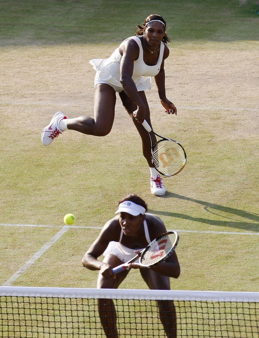 Serena Williams, left, of the U.S. serves as her sister Venus waits at the net during their doubles match against Dominika Cibulkova of Slovakia and Anastasia Pavlyuchenkova of Russia at the All England Lawn Tennis Championships at Wimbledon on Saturday, June 26, 2010. (AP Photo/Sang Tan)