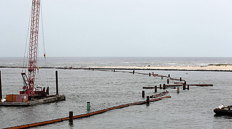 Pieces of a $4 million oil booming system in the Perdido Pass in Orange Beach, Ala., float in disarray Thursday, July 1, 2010 after six foot seas caused by Hurricane Alex battered the pass overnight. Officials said large bolts holding the structure together sheared off in the high seas.  They hope to have it back in place by Saturday. (AP Photo/Dave Martin)