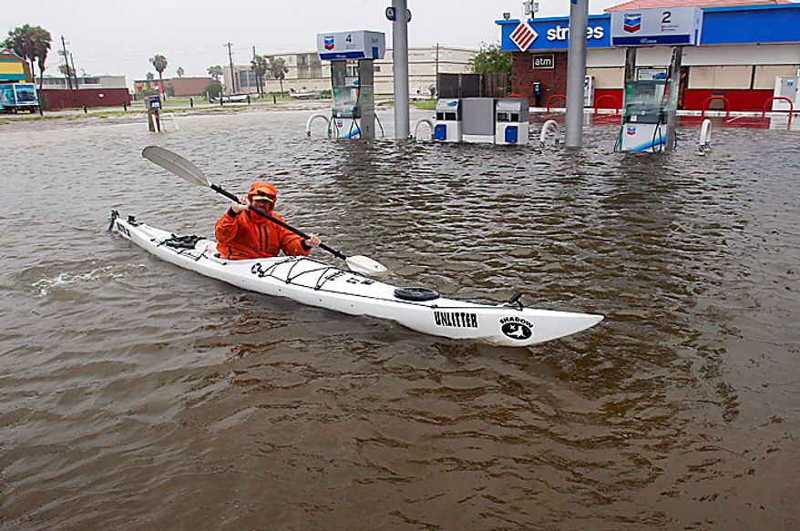 Dennis Barrett paddles his kayak down a flooded Padre Boulevard as the early effects of Hurricane Alex are felt along the Texas coast on Wednesday, June 30, 2010 in South Padre Island, Texas.  (AP Photo/Eric Gay)
