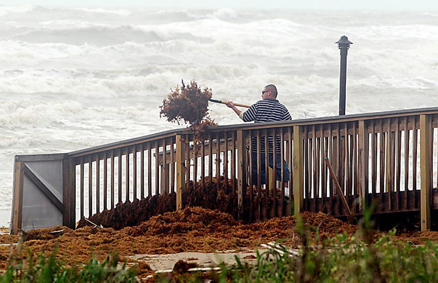 Sergio Alvarez shovels seaweed off a boardwalk as the lingering effects of Tropical Storm Alex are felt along the Texas coast on Thursday, July 1, 2010 in South Padre Island, Texas. The Atlantic season's first hurricane largely spared Texas, which had prepared for a possible direct hit. (AP Photo/Eric Gay)