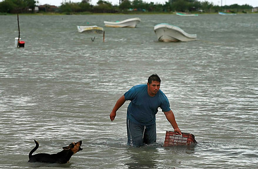 A man hauls a box to shore in preparation for the arrival of Hurricane Alex, the first Atlantic hurricane of the year, in La Carbonera, northeastern Mexico, on Wednesday, June 30, 2010. (AP Photo/Eduardo Verdugo)