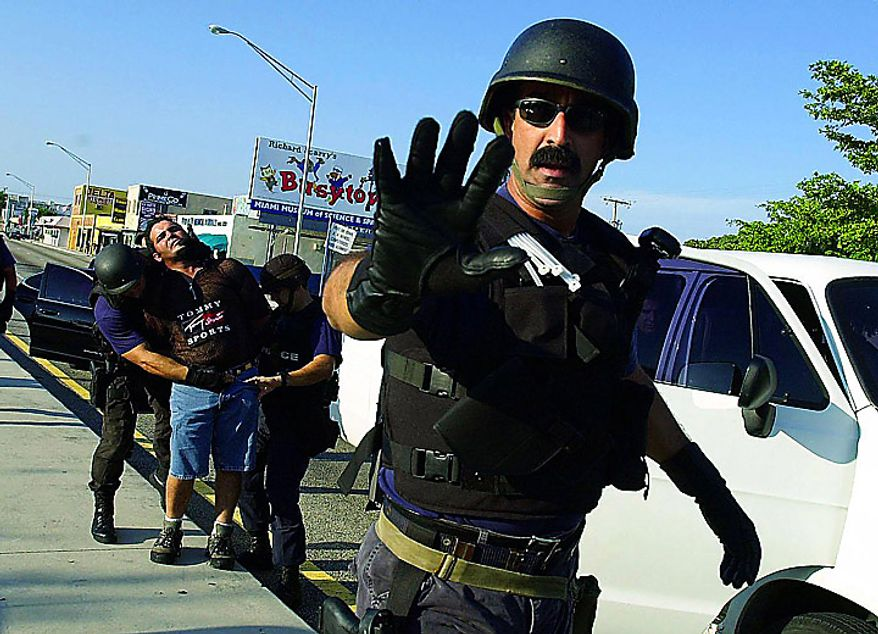 A Cuban American is arrested by Miami police in the aftermath of federal agents seizing Elian Gonzalez from the Little Havana home of relatives Sat., April 22, 2000. Some police (like this officer) threaten journalists with arrest for coming too close to arrests.  At least one TV photographer was arrested while covering the Miami unrest. ( Kenneth Lambert / The Washington Times )