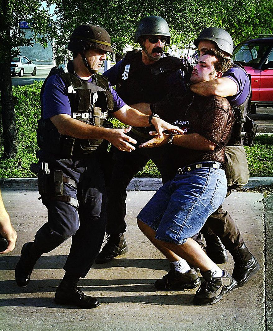 A Cuban American is arrested by Miami police in the aftermath of federal agents seizing Elian Gonzalez from the Little Havana home of relatives Sat., April 22, 2000. ( Kenneth Lambert / The Washington Times )