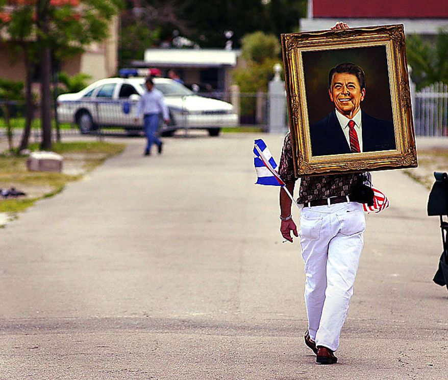 Monday outside Elian's house in Miami / ittle Havana. Gerado Barrios of Miami walks home with his portrait of Ronald Reagan as he leaves the area where Elian supporters have been hanging out, April 10, 2000. He said that Reagan was not afraid to fight communists. ( Sean Dougherty / The Washington Times )