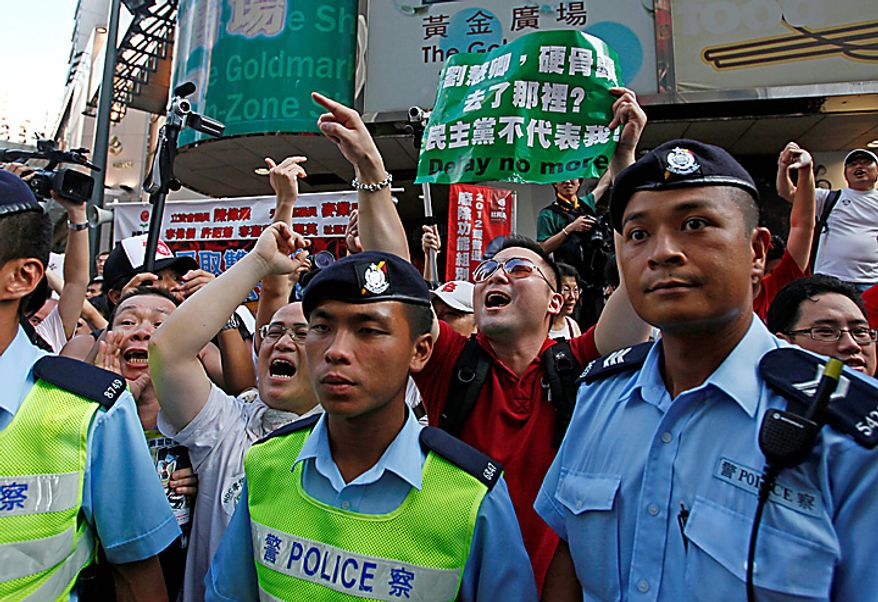 Protesters shout at the Democratic Party members behind police officers during a demonstration in Hong Kong on Thursday, July 1, 2010. Hecklers besieged Hong Kong's Democrats at the opposition camp's flagship protest march Thursday, accusing them of selling out their cause by striking a deal with Beijing on conservative electoral changes in the semiautonomous Chinese territory. (AP Photo/Kin Cheung)