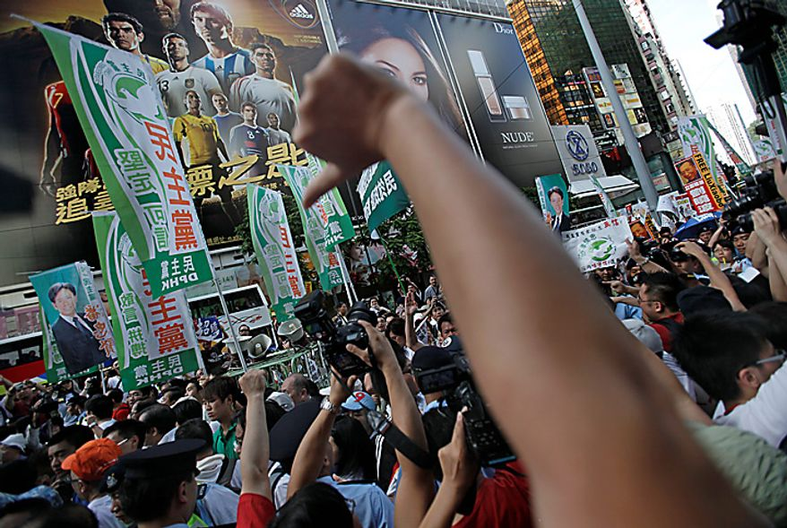 Protesters show thumb down sign against the Democratic Party members who took part in the annual pro-democracy march demanding universal suffrage in a downtown Hong Kong street on Thursday, July 1, 2010. Hecklers besieged Hong Kong's Democrats at the opposition camp's flagship protest march Thursday, accusing them of selling out their cause by striking a deal with Beijing on conservative electoral changes in the semiautonomous Chinese territory. (AP Photo/Vincent Yu)