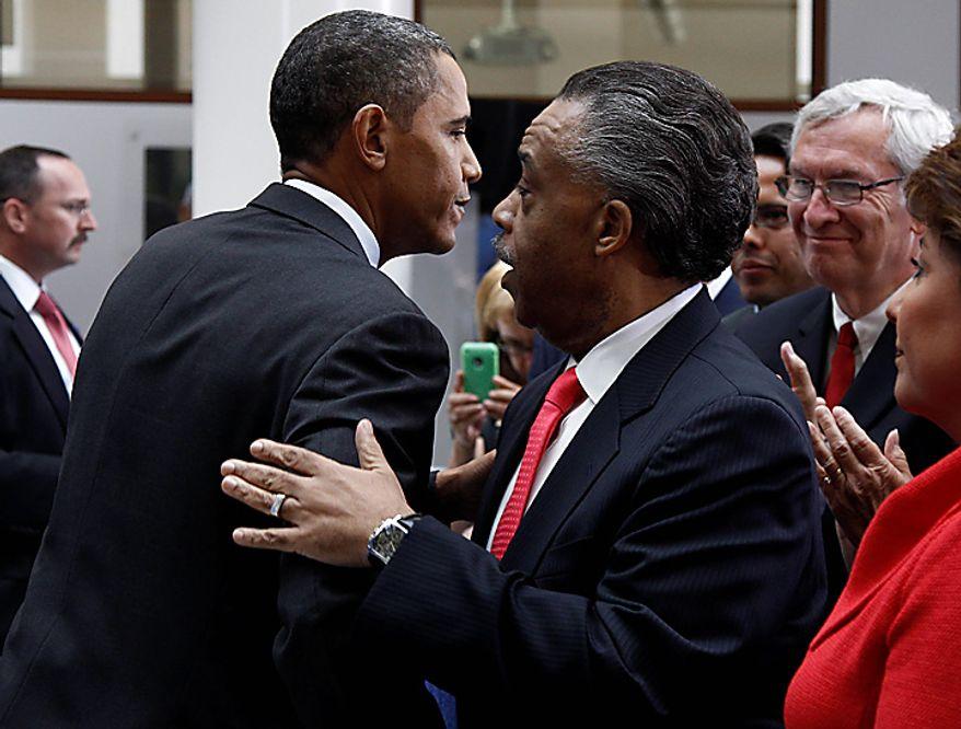 President Barack Obama is embraced by Rev. Al Sharpton after Obama spoke about immigration reform, Thursday, July 1, 2010, at American University in Washington. (AP Photo/Charles Dharapak)