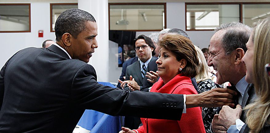 **FILE** President Obama adjusts the collar of Mort Zuckerman, chief executive officer of U.S. News and World Report (right), as Janet Murguia, president and CEO, National Council of La Raza, looks on, after Obama spoke about immigration reform on July 1, 2010, at American University in Washington. (Associated Press)