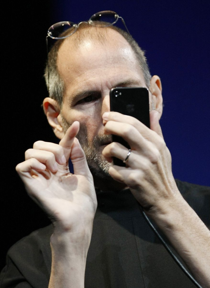 "In this June 7, 2010 photo, Apple CEO Steve Jobs uses the new iPhone 4, at the Apple Worldwide Developers Conference in San Francisco. Apple said Friday, July 2, it is ""stunned"" to find that its latest iPhone model uses a ""completely wrong"" formula to show how many bars of signal strength it's getting. (AP Photo/Paul Sakuma)"