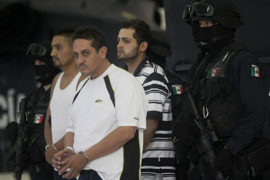 """Jesus Ernesto Chavez, known as """"El Camello,"""" second from left, stands as he is guarded by a federal police officer during a presentation to the press, in Mexico City, Friday, July 2, 2010. According to the federal police Chavez ordered the March 13 attack that killed a U.S. consulate employee and her husband as they drove in the violent border city. The other two detained men are unidentified. (AP Photo/Carlos Jasso)"""
