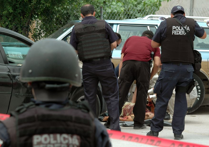 Forensic experts and federal police examine the body of a man that was killed by gunmen along with her 3 year-old daughter in the northern border city of Ciudad Juarez, Mexico, Tueday June 1, 2010. Ciudad Juarez has become one of the deadliest cities in the world as drug gangs are fighting an ongoing battle for smuggling routes. (AP Photo)