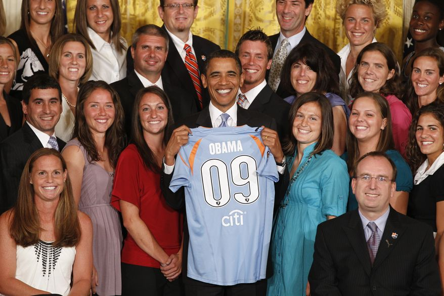 President Obama is presented with a team jersey from the Women's Professional Soccer Champions Sky Blue FC, Thursday, July 1, 2010, in the East Room of the White House in Washington, to honor their 2009 season and for winning the inaugural Women's Professional Soccer championship. Team captain Christie Rampone is pictured seated left. (AP Photo/Charles Dharapak)