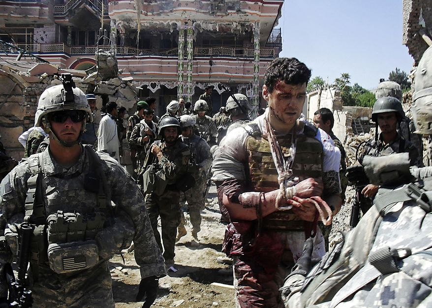 U.S. soldiers escort a wounded foreign contractor at a USAID compound in Kunduz, north of Kabul, Afghanistan, Friday, July 2, 2010, after it was stormed by militants wearing suicide vests. Six suicide bombers attacked the compound Friday in northern Afghanistan, killing at least four people and wounding several others, officials said.   (AP Photo)