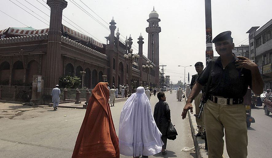 Pakistani police officers stand guard outside a mosque as authorities beefed up security in Peshawar, Pakistan on Friday, July 2, 2010, following suicide attacks on the shrine of Sufi Data Ganj Baksh in Lahore killing scores of people and left many injured. (AP Photo/Mohammad Sajjad)