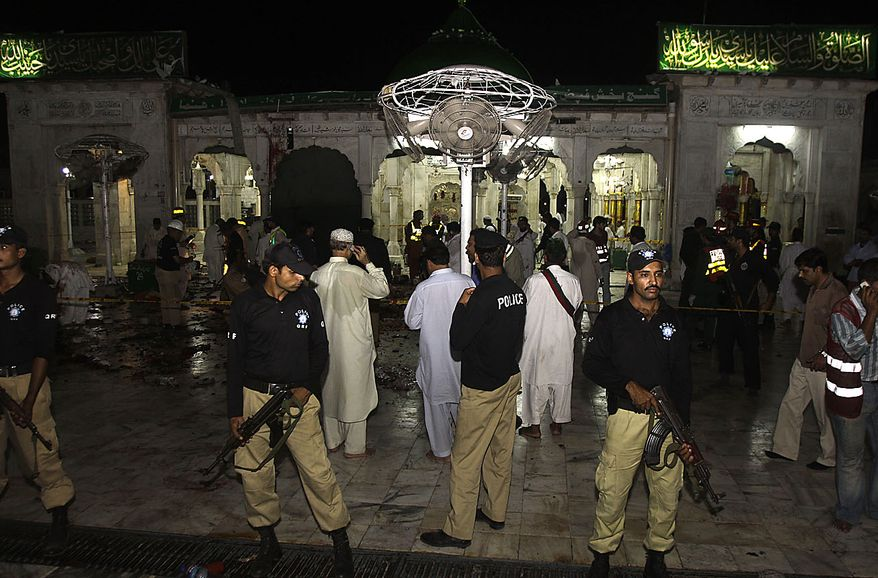 Pakistani police officers cordon off the area where suicide bombers attacked a popular Muslim shrine in the Pakistan city of Lahore late Thursday night July 1, 2010, killing more than 30 people and wounding 175 others, the city's top official said. (AP Photo/K.M.Chaudary)