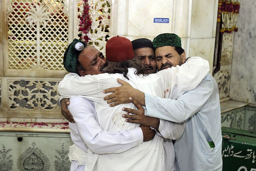 Family members of victims comfort each others after suicide bombers attacked a popular Muslim shrine in the Pakistan city of Lahore late Thursday night July 1, 2010, killing more than 30 people and wounding 175 others, the city's top official said. (AP Photo/K.M.Chaudary)