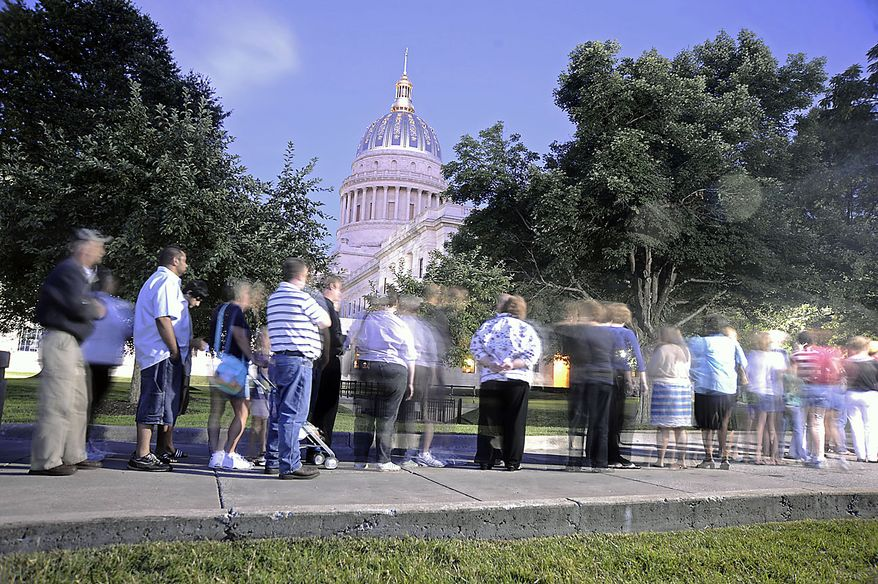 A line of people walk towards the Capitol to view the casket with Sen. Robert C. Byrd Thursday, July 1, 2010, in Charleston, W.Va. Mr. Byrd will lie in repose overnight at the Capitol until Friday morning when a memorial service will be held.  (AP Photo/Jeff Gentner)