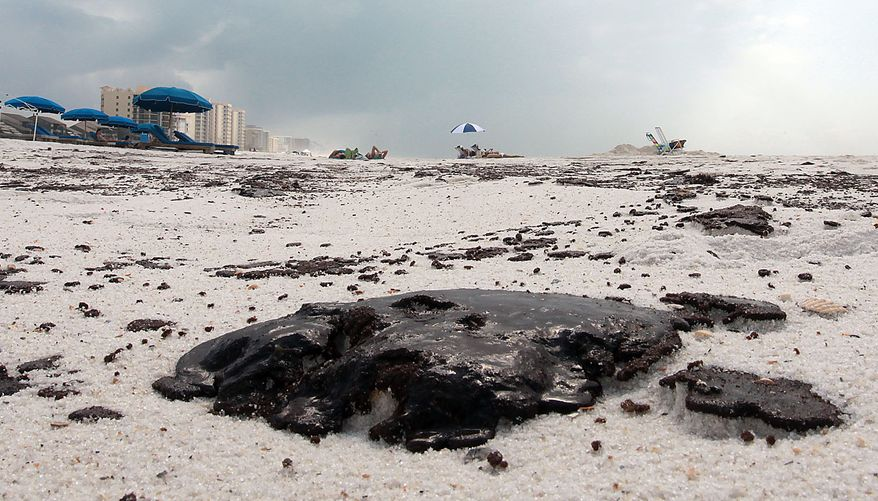 Tar balls sit on the beach in Perdido Key, Fla., Friday, July 2, 2010. Oil from the Deepwater Horizon incident is expected to continue to come ashore over the July 4th weekend and businesses are concerned about a lack of tourists. (AP Photo/Dave Martin)