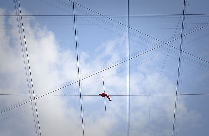 Adili Wuxor lies on a tightrope during the last day of his two-month tightrope walking performance on top of China's National Stadium, also known as the Bird's Nest, in Beijing Friday, July 2, 2010. Mr. Adili, an Uighur ethnic Dawaz tightrope walking performer, has been walking the tightrope five hours a day on the top of the Bird's Nest over the past 60 days, setting a new Guinness World Record. (AP Photo/Alexander F. Yuan)