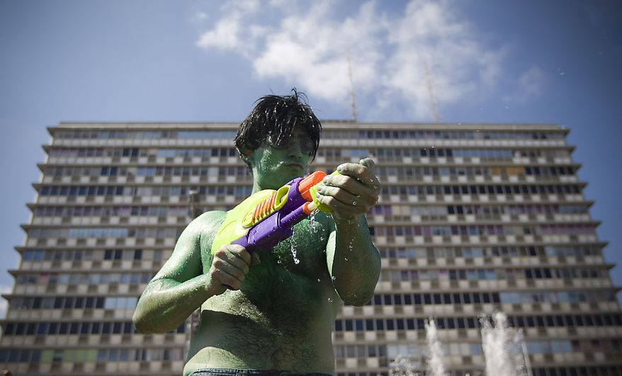 A person sprays water on others during a fun water fight event at Rabin Square in Tel Aviv, Israel, Friday, July 2, 2010. (AP Photo/Ariel Schalit)