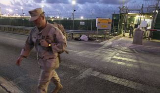 ** FILE ** In this May 13, 2009, file photo, reviewed by the U.S. military, a U.S. trooper walks near an entrance to the Guantanamo detention facility at dawn, at Guantanamo Bay U.S. Naval Base, Cuba. (AP Photo/Brennan Linsley)