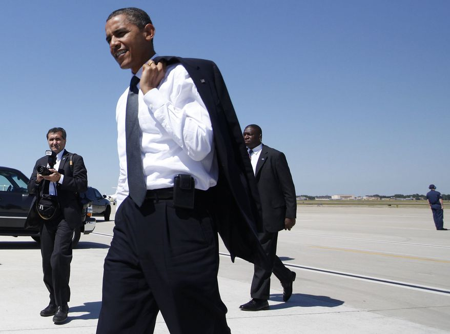 President Barack Obama, with his blazer slung over his shoulder, walks over to wish Air Force members and their families a Happy Fourth of July, at Andrews Air Force Base, Md., Friday, July 2, 2010, before boarding Marine One for a trip to Camp David, Md. At left is White House photographer Pete Souza. (AP Photo/Charles Dharapak)