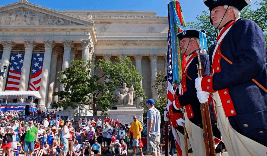 Soldiers in the 3rd U.S. Infantry Regiment Old Guard Continental Color Guard line up near the National Archives building in Washington before Fourth of July festivities Sunday. Meanwhile, the Obamas hosted members of the military and their families at a White House barbecue. (Associated Press)