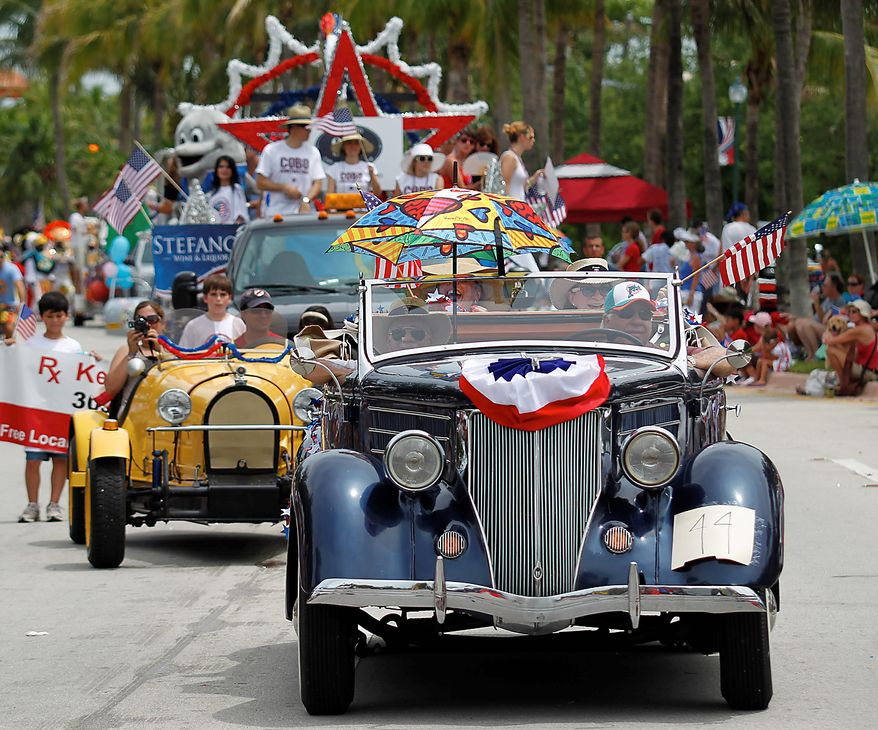 A 1936 Ford Cabriolet, foreground and a 1929 Bugatti Type 2 racer, left, participate in a Fourth of July parade in Key Biscayne, Fla., Sunday, July 4, 2010. (AP Photo/Wilfredo Lee)
