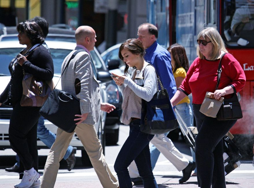 Head down, a woman texts while crossing an intersection in San Francisco. Experts say pedestrians are suffering the injury consequences of the texting distraction, but applications are being developed to lessen the hazard. (Associated Press)