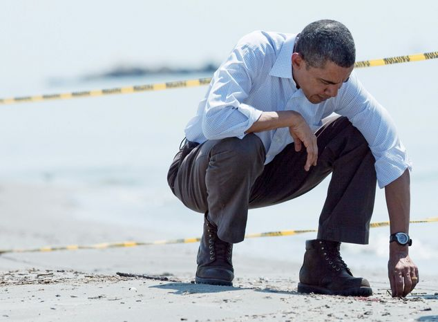 DEJA-VU: On May 28 this year, President Obama picks up a tar ball in Port Fourchon, La., while touring Gulf Coast areas impacted by the BP oil spill. (Associated Press)