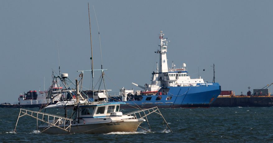 A boat skims oil in Mobile Bay near workboats and barges that sought refuge in the bay from Hurricane Alex near Dauphin Island, Ala., on Sunday, July 4, 2010. Oil from the Deepwater Horizon disaster continues to wash ashore along the Alabama and Florida coasts. (AP Photo/Dave Martin)