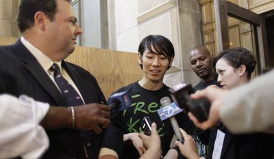 Six-time hot dog-eating contest champion Takeru Kobayashi, center, is joined by his attorney Mario D. Romano, left, and interpreter Maggie James as he speaks to reporters after leaving Brooklyn Criminal Court, Monday, July 5, 2010, in New York. Mr. Kobayashi was freed after a night in a New York jail after he pleaded not guilty to charges of obstruction of governmental administration, resisting arrest, trespassing and disorderly conduct. (AP Photo/Mary Altaffer)