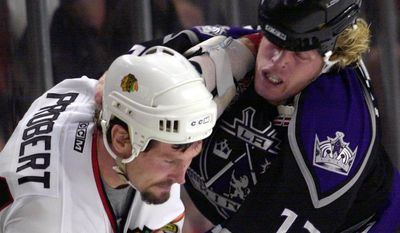 ASSOCIATED PRESS FILE - In this Oct. 30, 2001 photo, Chicago Blackhawks' Bob Probert (24) and Los Angeles Kings' Ken Belanger (12) mix it up in the third period of an NHL hockey game in Chicago. Probert has died after collapsing with severe chest pains while enjoying an afternoon of boating with his family. He was 45. Probert, one of the league's all-time great enforcers, Probert played for the Detroit Red Wings from 1985 to 1994, and for the Chicago Blackhawks from 1995 to 2002.