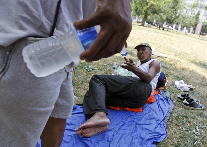 Vince Blackson with the United Planning Organization, a community action group, gives water to Michael Smith, who is laying in the shade in the hot weather in Washington Tuesday, July 6, 2010. (AP Photo/Alex Brandon)