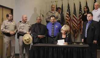 ** FILE ** Arizona Gov. Jan Brewer, with law enforcement supporters behind her, signs immigration bill SB 1070 into law in Phoenix on April 23, 2010. (AP Photo)