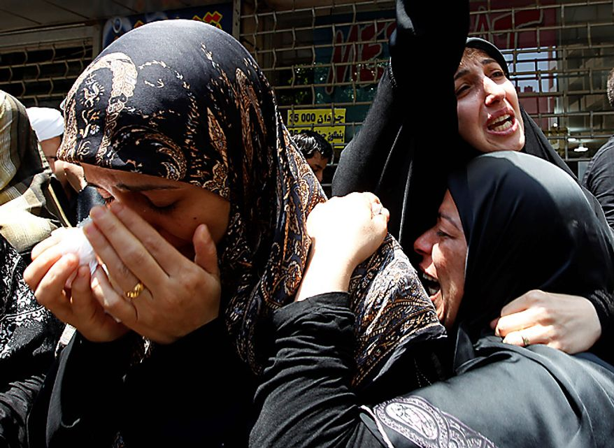 Lebanese Shiite women mourn during the funeral procession of Lebanon's top Shiite cleric Grand Ayatollah Mohammed Hussein Fadlallah, who died on Sunday, at the southern suburb of Beirut, Lebanon, on Tuesday, July 6, 2010. Tens of thousands of people swarmed the coffin of Lebanon's top Shiite cleric as it made its way through the streets of south Beirut to the mosque for burial. (AP Photo/Hussein Malla)