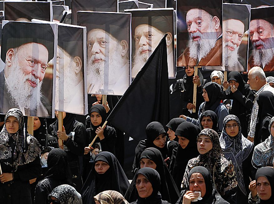 Shiite women mourn as they hold posters of Lebanon's top Shiite cleric Grand Ayatollah Mohammed Hussein Fadlallah, who died on Sunday, during his funeral procession at the southern suburb of Beirut, Lebanon, on Tuesday, July 6, 2010. The cleric was one of Shiite Islam's highest authorities and most revered religious figures. (AP Photo/Hussein Malla)