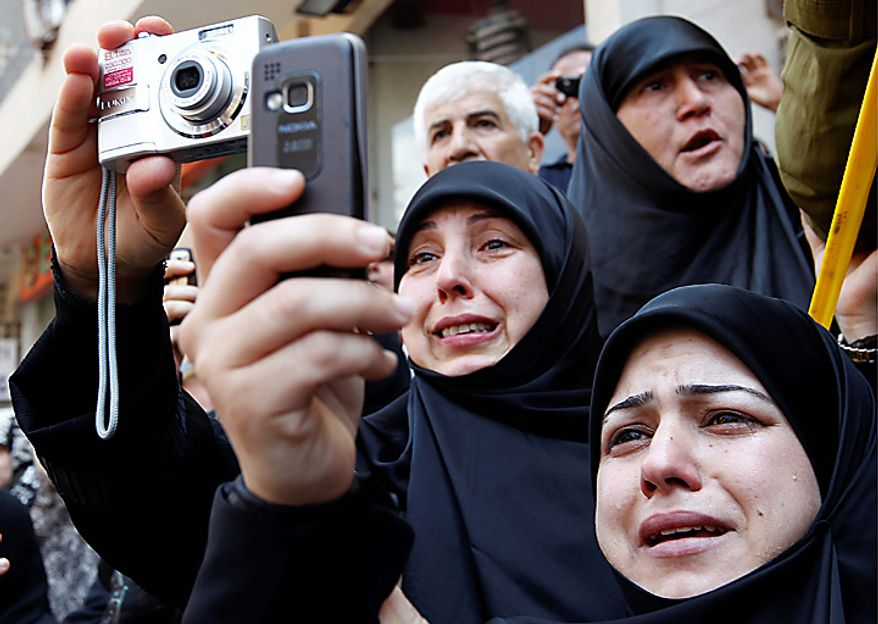Lebanese Shiite women mourn as they take pictures for the coffin of Lebanon's top Shiite cleric Grand Ayatollah Mohammed Hussein Fadlallah, who died on Sunday, during his funeral procession at the southern suburb of Beirut, Lebanon, on Tuesday, July 6, 2010. Grand Ayatollah Mohammed Hussein Fadlallah, 75, died Sunday after a long illness. (AP Photo/Hussein Malla)