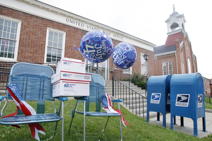 """In this June 29, 2010 photo, a pair of blue chairs decorated with holiday balloons and the postal services """"flat-rate"""" boxes are on the lawn in front of the post office in Canonsburg, Pa. Postal officials scheduled a briefing Tuesday, July 6, 2010 to discuss the amount of the increase, which will go to the independent Postal Regulatory Commission for review. (AP Photo/Keith Srakocic)"""