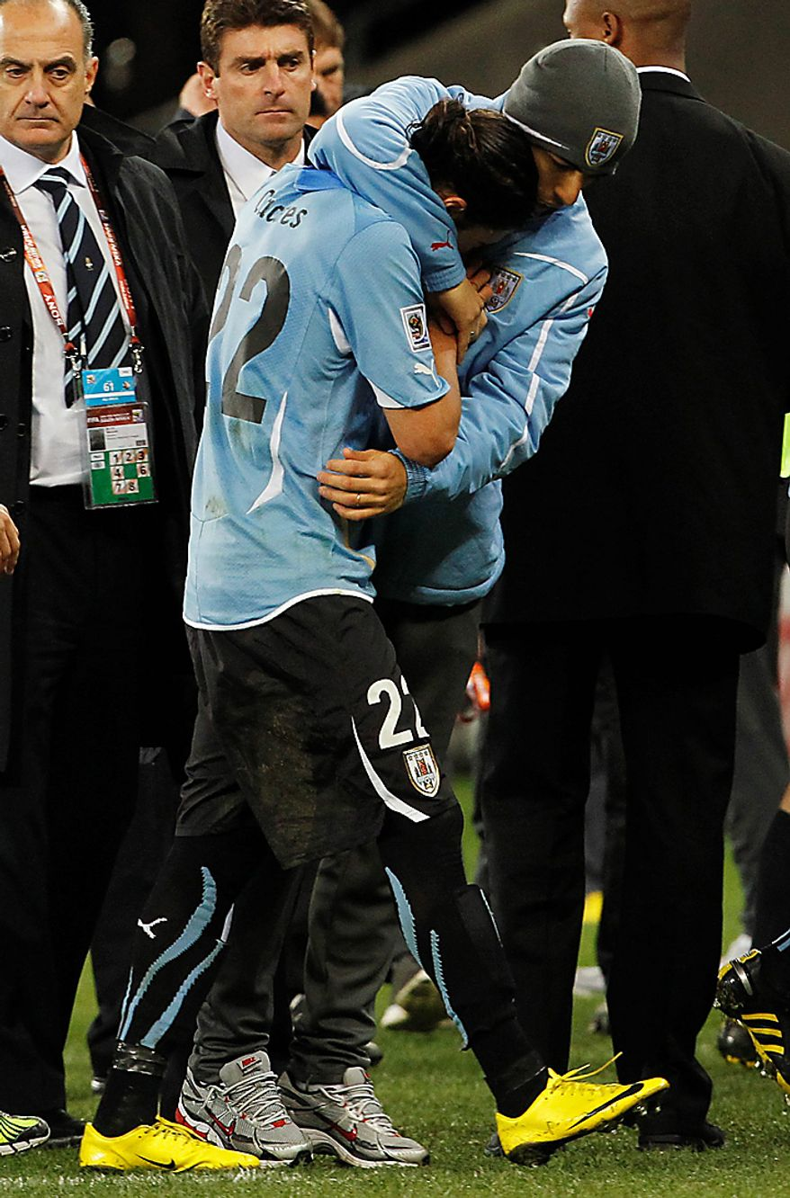 Uruguay's Martin Caceres, center foreground, is comforted by a fellow team member following the World Cup semifinal soccer match between Uruguay and the Netherlands at the Green Point stadium in Cape Town, South Africa, Tuesday, July 6, 2010. Netherlands defeated Uruguay 3-2. (AP Photo/Bernat Armangue)