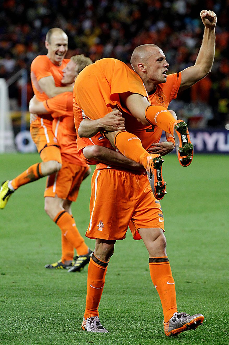 Netherlands' John Heitinga, front right, carries Netherlands' Wesley Sneijder, front left, as they celebrate following the World Cup semifinal soccer match between Uruguay and the Netherlands at the Green Point stadium in Cape Town, South Africa, Tuesday, July 6, 2010. Netherlands defeated Uruguay 3-2. (AP Photo/Schalk van Zuydam)