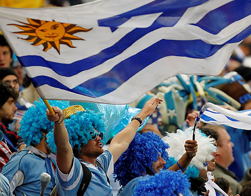 Supporters of Uruguay wave flags before the World Cup semifinal soccer match between Uruguay and the Netherlands at the Green Point stadium in Cape Town, South Africa, Tuesday, July 6, 2010.  (AP Photo/Bernat Armangue)