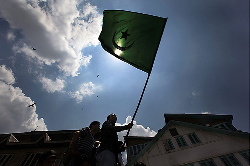 Kashmiris shout freedom slogans as they wave an Islamic flag during a protest march against the killings of two youths in Srinagar, India, Tuesday, July 6, 2010. Government forces fired on hundreds of rock-throwing protesters in Indian Kashmir on Tuesday, killing Fayaz Ahamed Wani and wounding two others as a seven-day curfew was lifted, locals and officials said. Another boy Muzaffar Bhat was allegedly killed by paramilitary soldiers Monday. (AP Photo/Dar Yasin)