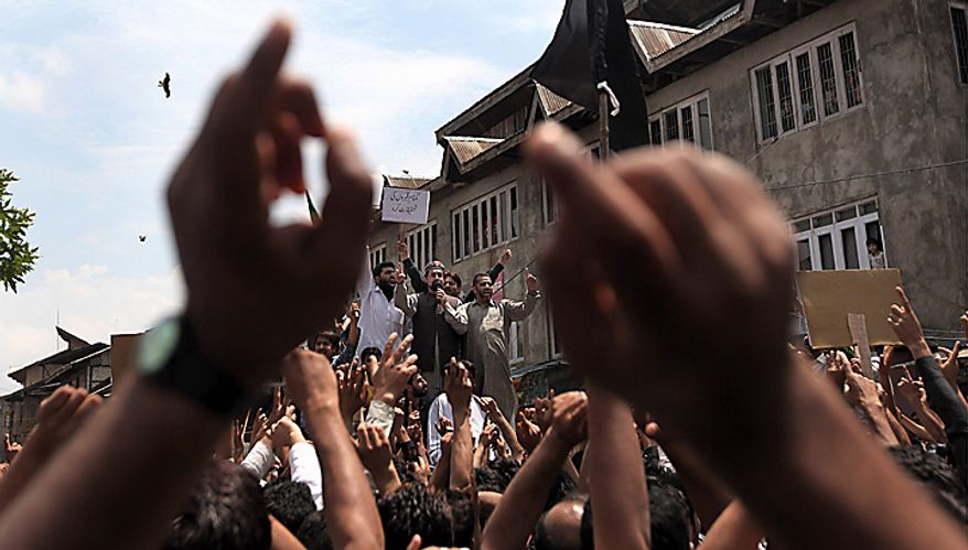 Chairman of the All Parties Hurriyat Conference Mirwaiz Umar Farooq, center top, shouts freedom slogans during a protest march against the fresh killings of two youths in Srinagar, India, Tuesday, July 6, 2010. Government forces fired on hundreds of rock-throwing protesters in Indian Kashmir on Tuesday, killing one person and wounding two others as a seven-day curfew was lifted, locals and officials said. Another youth Muzaffar Bhat was allegedly killed by paramilitary soldiers Monday. (AP Photo/Dar Yasin)